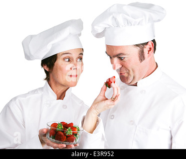 One chef offers another a fresh strawberry. Isolated on white.  - Stock Photo