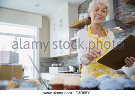 Woman with clipboard baking cupcakes in kitchen - Stock Photo