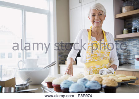Woman baking cupcakes in kitchen - Stock Photo