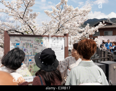 Japanese tourists reading a local sightseeing guide map in Kyoto, Japan. - Stock Photo