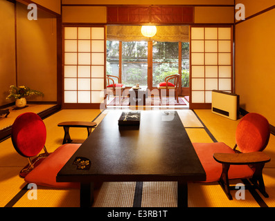 Japanese room interior at a ryokan with garden view in Kyoto, Japan. Tea table chabudai and zaisu chairs. - Stock Photo