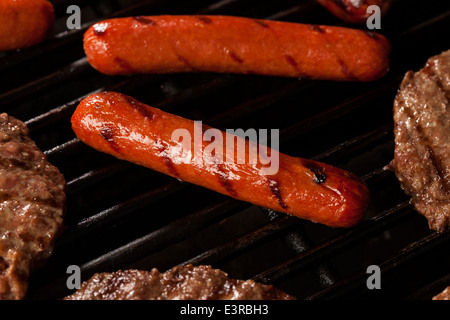 Delicious Hamburgers and Hot Dogs on the Grill - Stock Photo