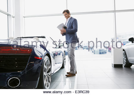 Man looking at convertible in car dealership showroom - Stock Photo