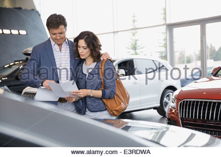 Couple looking at brochure in car dealership showroom - Stock Photo