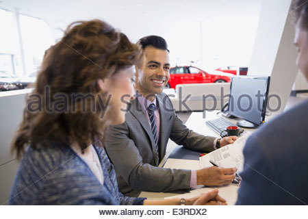 Salesman and couple finalizing paperwork in car dealership - Stock Photo