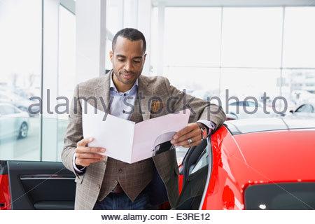 Man looking at brochure in car dealership showroom - Stock Photo