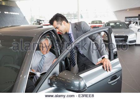 Salesman and man looking inside car in showroom - Stock Photo