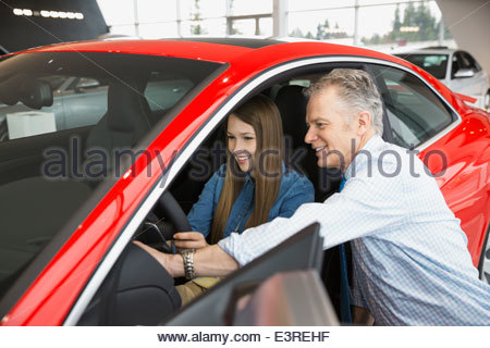 Salesman and woman looking inside car in showroom - Stock Photo
