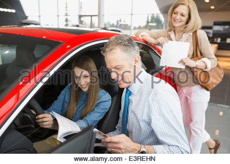 Family looking at car in car dealership showroom - Stock Photo