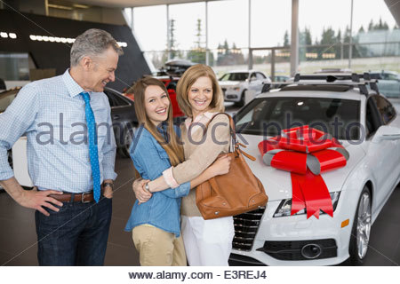 Parents buying daughter car in dealership showroom - Stock Photo