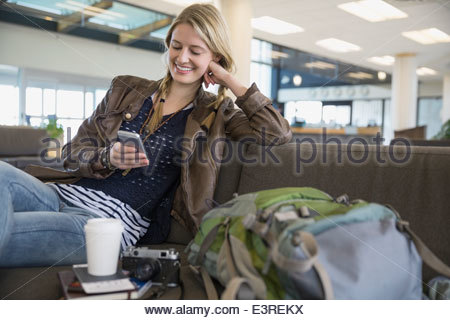 Woman with backpack and cell phone in airport - Stock Photo