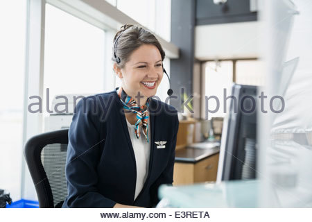 Flight attendant with headset at computer in airport - Stock Photo