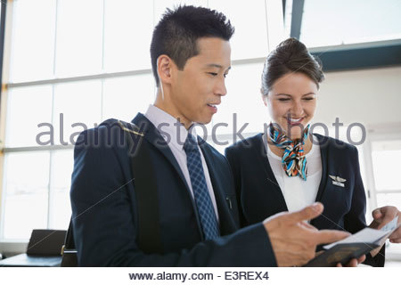 Airport customer service representative helping businessman - Stock Photo