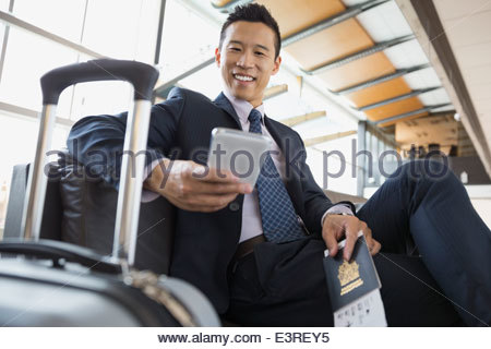 Businessman with cell phone waiting in airport - Stock Photo