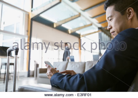 Businessman using cell phone in airport - Stock Photo