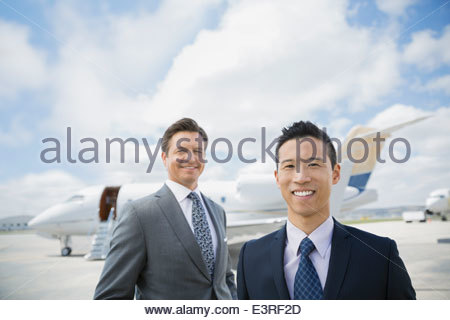 Portrait of businessmen on tarmac with corporate jet - Stock Photo