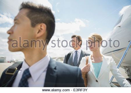 Business people on tarmac near corporate jet - Stock Photo