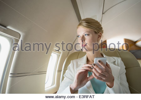 Businesswoman text messaging on corporate jet - Stock Photo