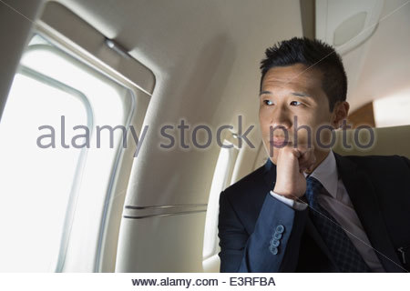 Pensive businessman looking at window of corporate jet - Stock Photo