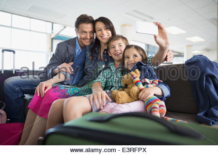 Family taking selfie in airport - Stock Photo