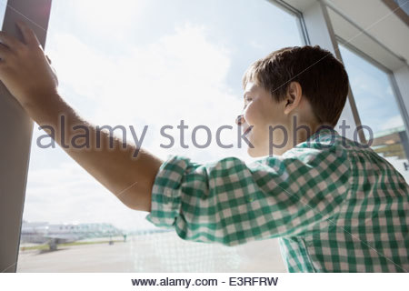 Boy looking at airport window - Stock Photo