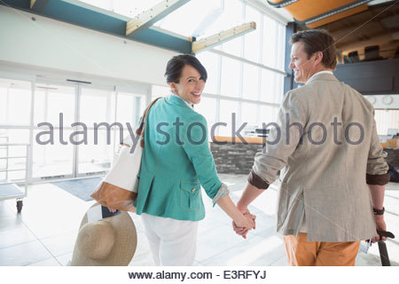Smiling couple holding hands in airport - Stock Photo