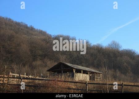 Traditional Romanian sheepfold in green landscape.