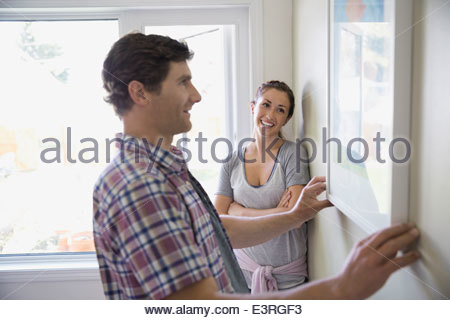 Couple hanging painting on living room wall - Stock Photo