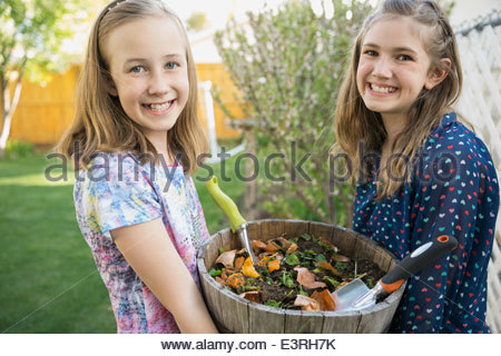 Portrait of smiling girls holding flowerpot in garden - Stock Photo