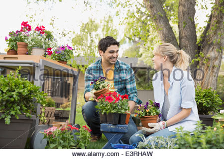 Couple planting flowers in garden - Stock Photo