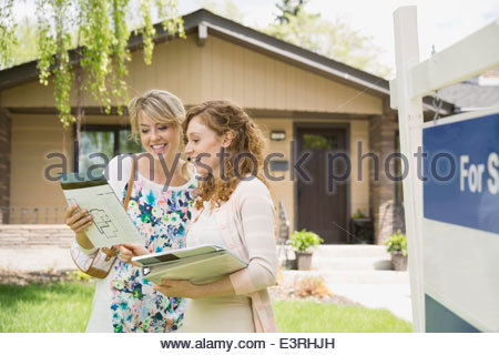 Realtor showing woman paperwork outside house - Stock Photo