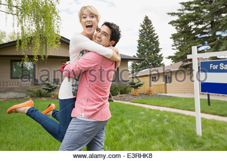 Couple celebrating outside house with For Sale sign - Stock Photo