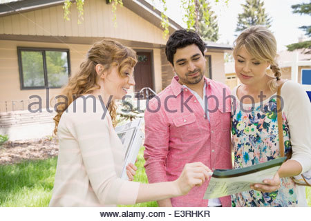 Realtor showing couple paperwork outside house - Stock Photo