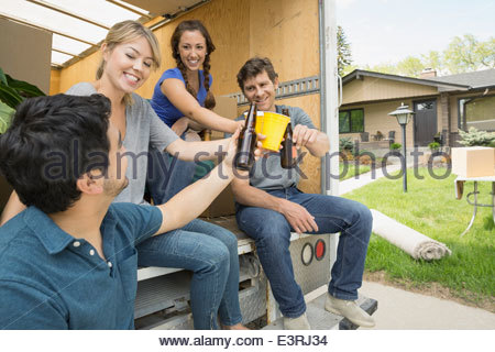 Couples toasting beer at back of moving van - Stock Photo