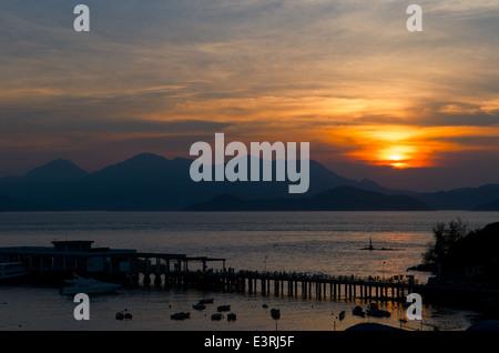 sunset over the Lamma Island ferry pier, Yung Shue Wan, Lamma Island, Hong Kong, China - Stock Photo