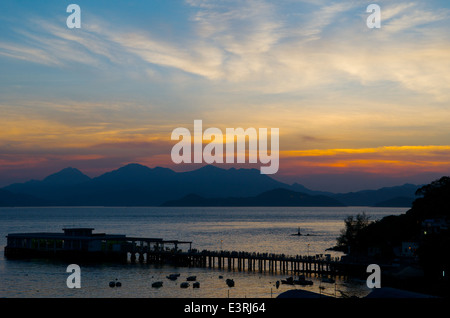 sunset / sundown over the Lamma Island ferry pier, Yung Shue Wan, Lamma Island, Hong Kong, China. credit: Kraig - Stock Photo