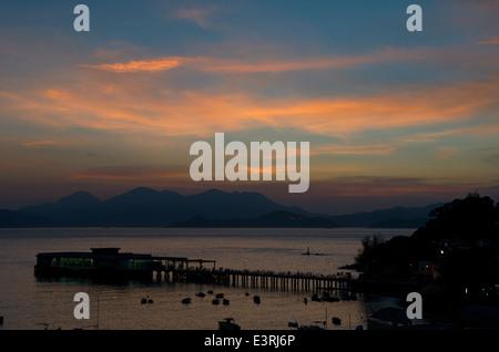 sunset / sundown over the Lamma Island ferry pier, Yung Shue Wan, Lamma Island, Hong Kong, China. credit; Kraig - Stock Photo