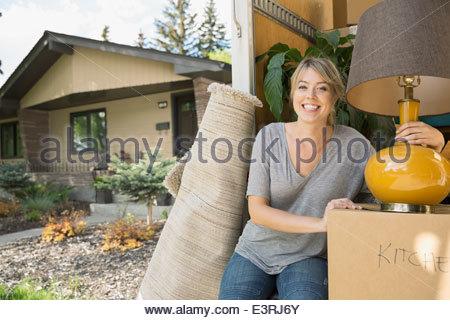 Portrait of woman unloading belongings from moving van - Stock Photo