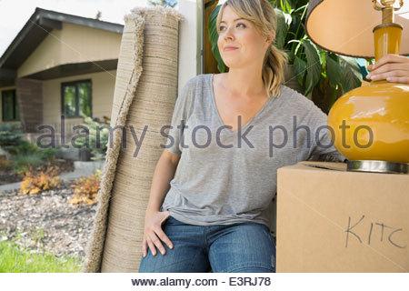 Woman unloading belongings from moving van - Stock Photo