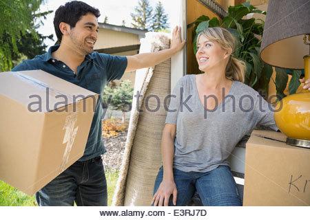 Couple unloading belongings from moving van - Stock Photo