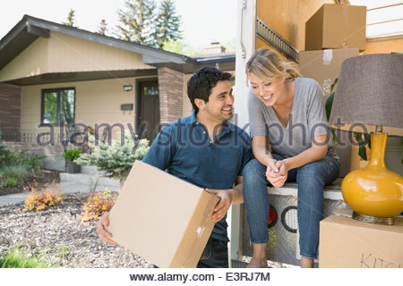 Couple talking at back of moving van - Stock Photo