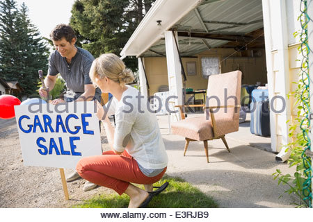Couple putting up garage sale sign in yard - Stock Photo