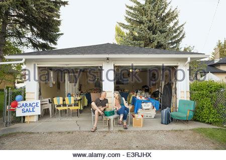 Couple sitting outside of garage sale - Stock Photo