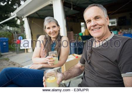 Portrait of couple drinking lemonade outside garage sale - Stock Photo