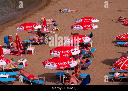 People Sunbathing On a Sandy beach On Sunloungers Under Parasols - Stock Photo