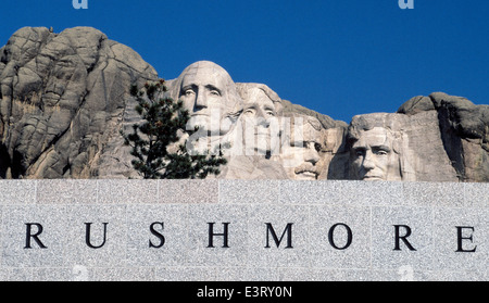 The faces of four U.S. Presidents carved on a mountain look over a Mount Rushmore National Memorial sign in the - Stock Photo