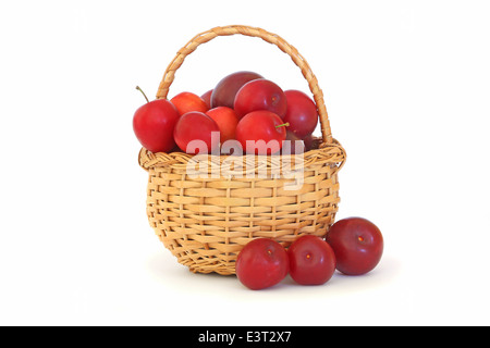 Plums in a wicker basket isolated on white background - Stock Photo