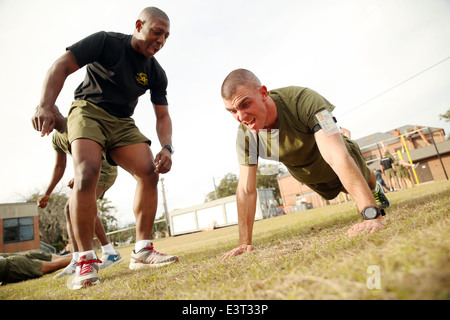 A US Marine Corps Drill Instructor encourages student Staff Sgt. Joseph McNichols to move with intensity during - Stock Photo