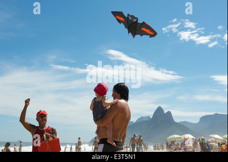 RIO DE JANEIRO, BRAZIL - MARCH 10, 2013: A beach vendor selling kits displays his merchandise for a father and child - Stock Photo