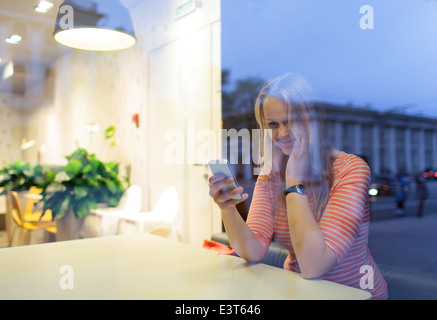 Smiling woman in cafe reading or typing sms - Stock Photo
